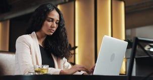 Jeune femme soumise à une contrainte d'affaires avec le fonctionnement d'ordinateur portable au café Affaires dures, les gens, da clips vidéos
