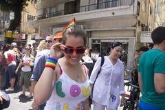 Jeune femme souriant à l'appareil-photo au défilé de fierté Photographie stock libre de droits