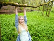 Jeune femme souriant et accrochant sur une branche Image libre de droits