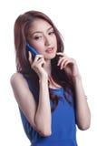 Jeune femme souriant et textotant à son téléphone portable Photos stock