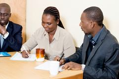 Jeune femme souriant prenant des notes au cours d'une réunion d'affaires Images stock