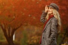 Jeune femme souriant sur le fond rouge de jardin image stock