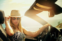 Jeune femme souriante d'un air affecté au volant Photos stock