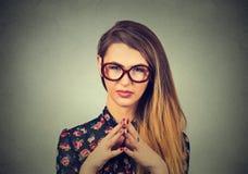 Jeune femme sournoise, astucieuse, intrigante en verres traçant quelque chose Images libres de droits