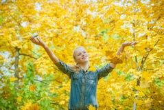Jeune femme sous la douche des feuilles d'autmn Images stock