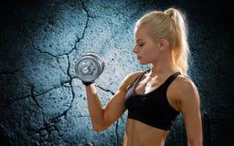 Jeune femme sportive avec l'haltère en acier lourde Photographie stock