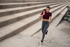 Jeune femme sportive courant sur des escaliers Images stock