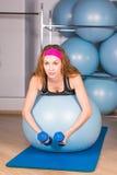 Jeune femme sportive dans le gymnase faisant l'exercice de forme physique avec la boule bleue Photographie stock