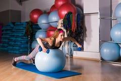 Jeune femme sportive dans le gymnase faisant l'exercice de forme physique avec la boule bleue Image libre de droits