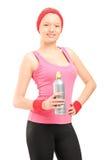 Jeune femme sportive dans les vêtements de sport retenant une bouteille de l'eau Photos libres de droits