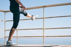 Jeune femme sportive faisant étirant des jambes sur la plage en m Images stock