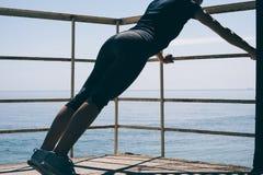 Jeune femme sportive faisant des pousées pendant le matin sur la plage photographie stock