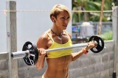 Jeune femme sportive faisant la séance d'entraînement avec le barbell extérieur Images stock