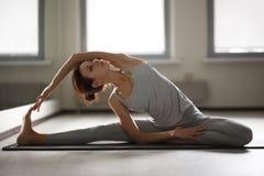 Jeune femme sportive faisant le yoga étirant l'exercice se reposant dans le gymnase près des fenêtres lumineuses Images stock