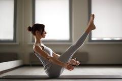 Jeune femme sportive faisant le yoga étirant l'exercice se reposant dans le gymnase près des fenêtres lumineuses Images libres de droits