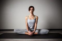 Jeune femme sportive faisant le yoga étirant l'exercice se reposant dans le gymnase près des fenêtres lumineuses Photo stock