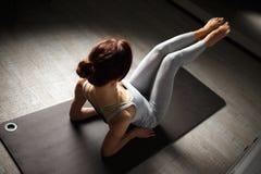 Jeune femme sportive faisant le yoga étirant l'exercice se reposant dans le gymnase près des fenêtres lumineuses Photo libre de droits