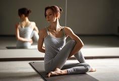Jeune femme sportive faisant le yoga étirant l'exercice se reposant dans le gymnase près des fenêtres lumineuses Photographie stock libre de droits