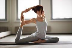 Jeune femme sportive faisant le yoga étirant l'exercice se reposant dans le gymnase près des fenêtres lumineuses Photographie stock