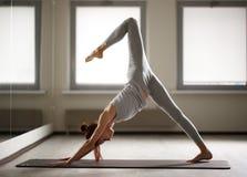 Jeune femme sportive faisant le yoga étirant l'exercice se reposant dans le gymnase près des fenêtres lumineuses Image stock