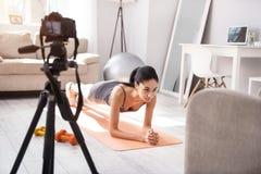 Jeune femme sportive faisant un exercice de planche et se filmant Photos libres de droits