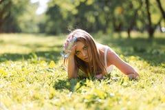 Jeune femme sportive heureuse dans les v?tements de sport avec de l'eau se reposant sur l'herbe apr?s avoir puls? en parc de vill photos libres de droits