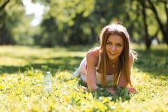 Jeune femme sportive heureuse dans les v?tements de sport avec de l'eau se reposant sur l'herbe apr?s avoir puls? en parc de vill photo stock