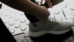 Jeune femme sportive mettant une courroie sur son Shin For Leg Exercises banque de vidéos