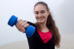 Jeune femme sportive s'exerçant avec des dumbells pendant le train de forme physique Image libre de droits