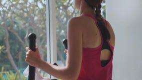 Jeune femme sportive s'exerçant sur la machine d'étape au gymnase dans le mouvement lent banque de vidéos