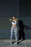 Jeune femme sportive tenant des poids se tenant sur le fond noir de mur au coucher du soleil Photographie stock
