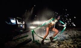Jeune femme sportive tirant la voiture en hiver Photos stock