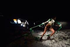 Jeune femme sportive tirant la voiture en hiver Image libre de droits