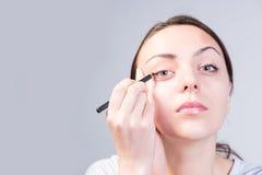 Jeune femme sérieuse appliquant l'eye-liner sur l'oeil droit Photographie stock libre de droits