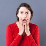 Jeune femme stupéfaite avec l'expression chutante de mâchoire touchant son visage Photographie stock libre de droits