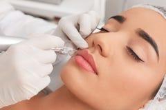 Jeune femme subissant la procédure de la lèvre permanente images libres de droits