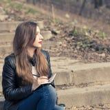 Jeune femme sur des escaliers dans l'écriture de parc dans la protection Photos libres de droits
