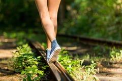 Jeune femme sur des rails dans des espadrilles Photos libres de droits