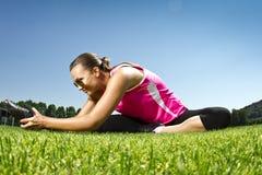 Jeune femme sur frais l'étirage d'herbe de coupure image stock