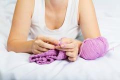 Jeune femme sur la laine de crochet de lit Photo libre de droits
