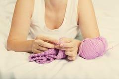 Jeune femme sur la laine de crochet de lit Image libre de droits