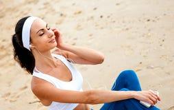 Jeune femme sur la plage écoutant la musique Photo libre de droits