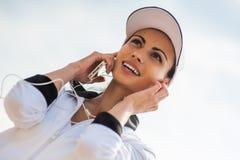 Jeune femme sur la plage écoutant la musique Photographie stock libre de droits