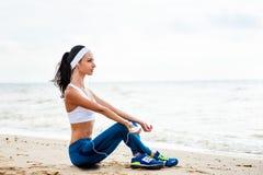 Jeune femme sur la plage écoutant la musique Photos libres de droits