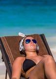 Jeune femme sur la plage dans des lunettes de soleil Image stock