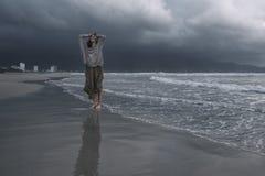 Jeune femme sur la plage de la mer déchaînée au jour pluvieux photographie stock libre de droits