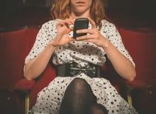 Jeune femme sur la première ligne de salle de cinéma utilisant son téléphone images stock