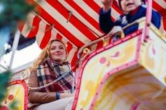 Jeune femme sur la roue de ferris sur le marché de Noël Photos stock