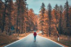 Jeune femme sur la route dans la forêt d'automne au coucher du soleil photos libres de droits