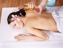 Jeune femme sur la table de massage dans la station thermale de beauté. photo stock
